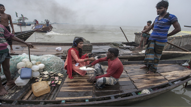 A young girl interviews a local fisherman in Bangladesh. Picture credit: COAST