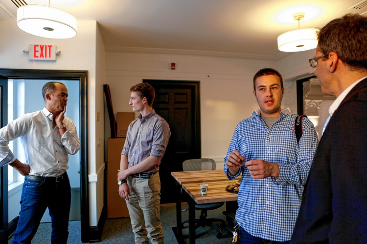 Tim Mitrovich of Kayon Accelerator, left, UMass Amherst student Eli Bucher, Bryon Wells of Amherst and David Vogel of Kayon Accelerator talk Dec. 14, 2016 at AmherstWorks coworking space on Amity Street. Kayon Accelerator is a new Amherst-based entity that will help entrepreneurs with seed capital and hands-on assistance starting in February. In exchange, Kayon will take ownership in small pieces of the companies it invests in.    —GAZETTE STAFF/SARAH CROSBY