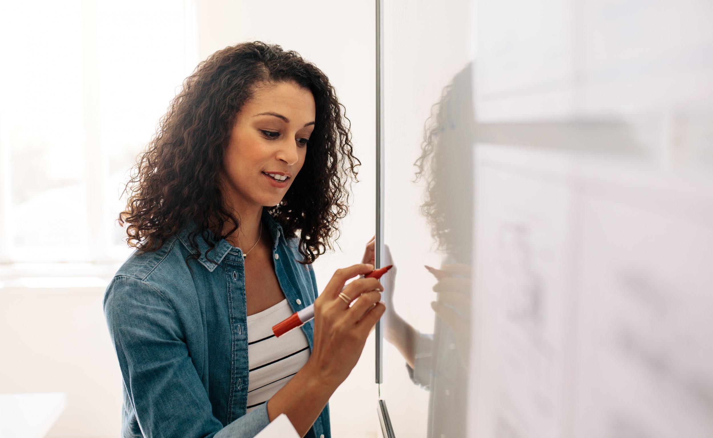Canva - Businesswoman Writing on Whiteboard in Office.jpg
