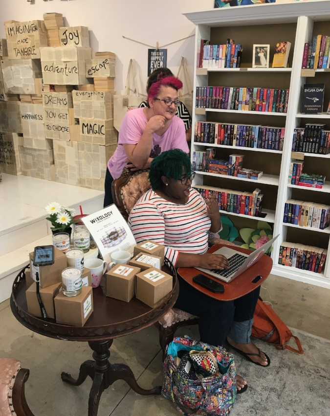 """Rebekah Weatherspoon (with a fan,at the computer) and Sarah Kuhn (right) are both romance writers who love to hang out – and work! – at the """"Ripped Bodice"""". Rebekah loves comedy, Sarah's heroine is some sort of ninja, and both are proud feminists"""