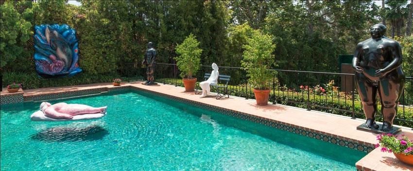 """Rosige Aussichten: """"Freundin Inge"""", eine beleibte und beliebte Installation, döst auf ihrer Pappmaché-Matratze im Pool der Weisman-Villa in Holmby Hills. Vorne rechts, dito üppig, eine Skulptur von Botero: Nicht nur künstlerisch gesehen, trifft man hier viele Schwergewichte"""