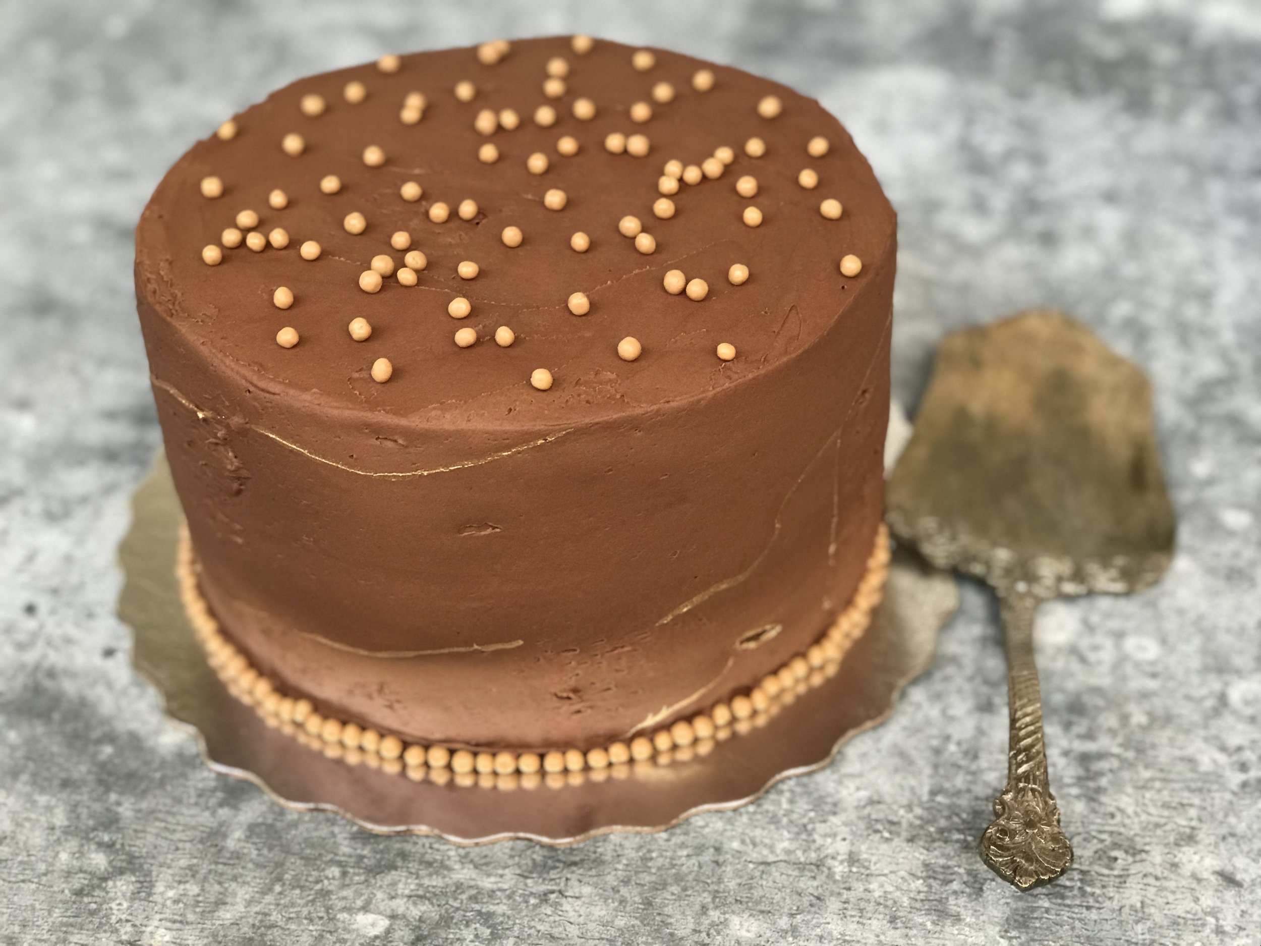 Chocolate cake with chocolate frosting. Decorated with Callebaut Crispearls: salted caramel