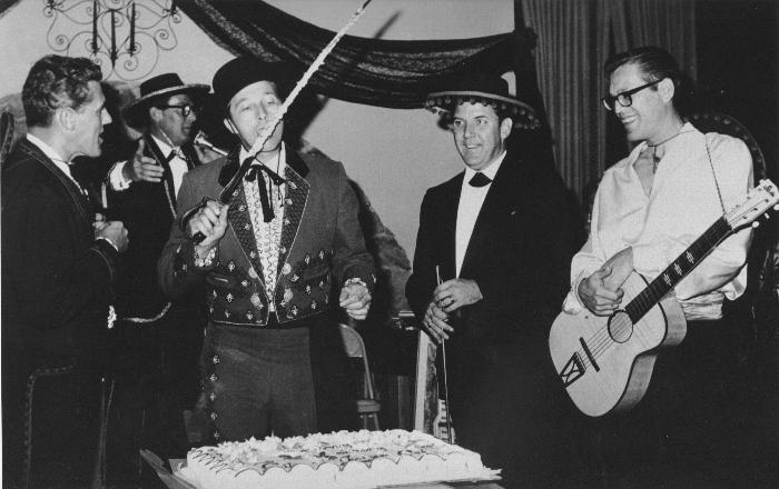 At the Triunfo Ball, 1966. L to R: John Tapking, Councilman; David Betts, former Mayor; Robert Talley, Councilman; Alex Fiore, Councilman. In the rear at the mike is Guy Runion, former owner and editor of the Conejo News.