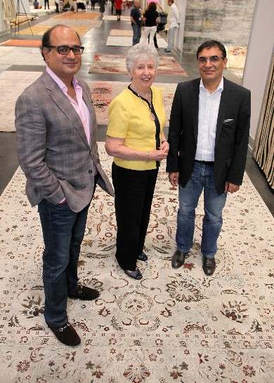 Sanjay Purohit, left, and Reza Zollanvari, right, with Art to Walk On's Eileen Hampshire, who bought the silk and oxidized wool rug the trio is posing on.