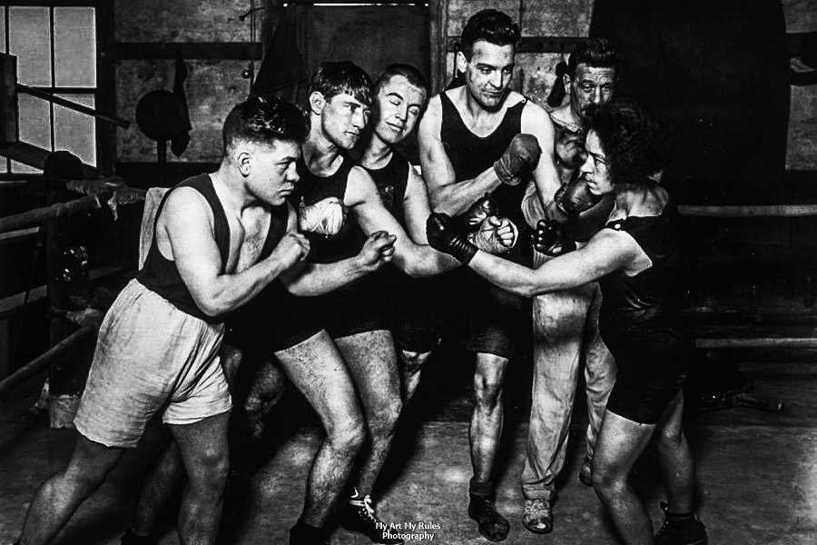 Female boxer Annie Newton poses in a face-off with five men. Fox Photos/Getty Images
