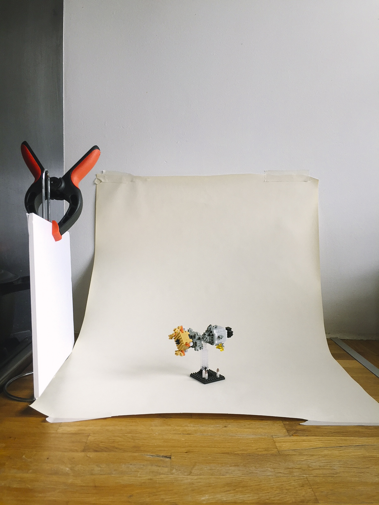 This simple setup was created with masking tape, butcher's paper and a piece of white card to fill in some shadows. Notice how the paper is taped slightly away from the wall to create a nice curve; this gives you a seamless backdrop. The white card is placed opposite the window to soften the shadow.