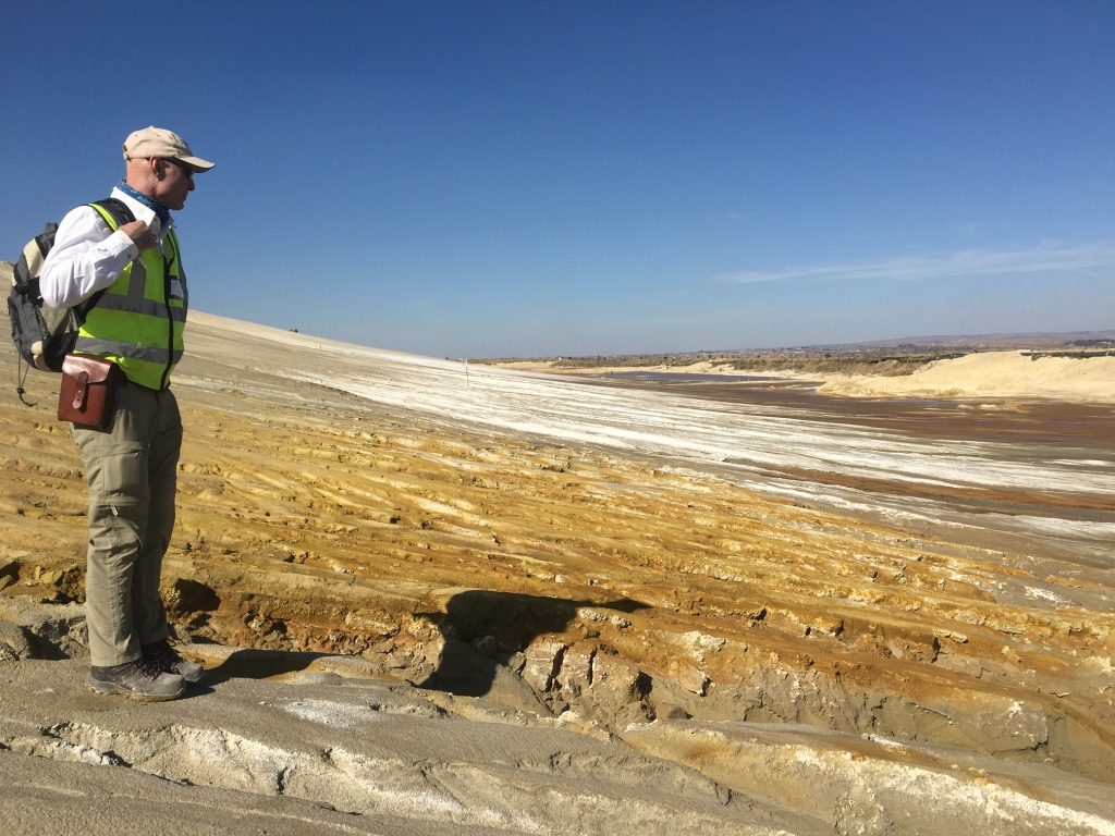 Collecting samples of acid seepage from gold mine tailings