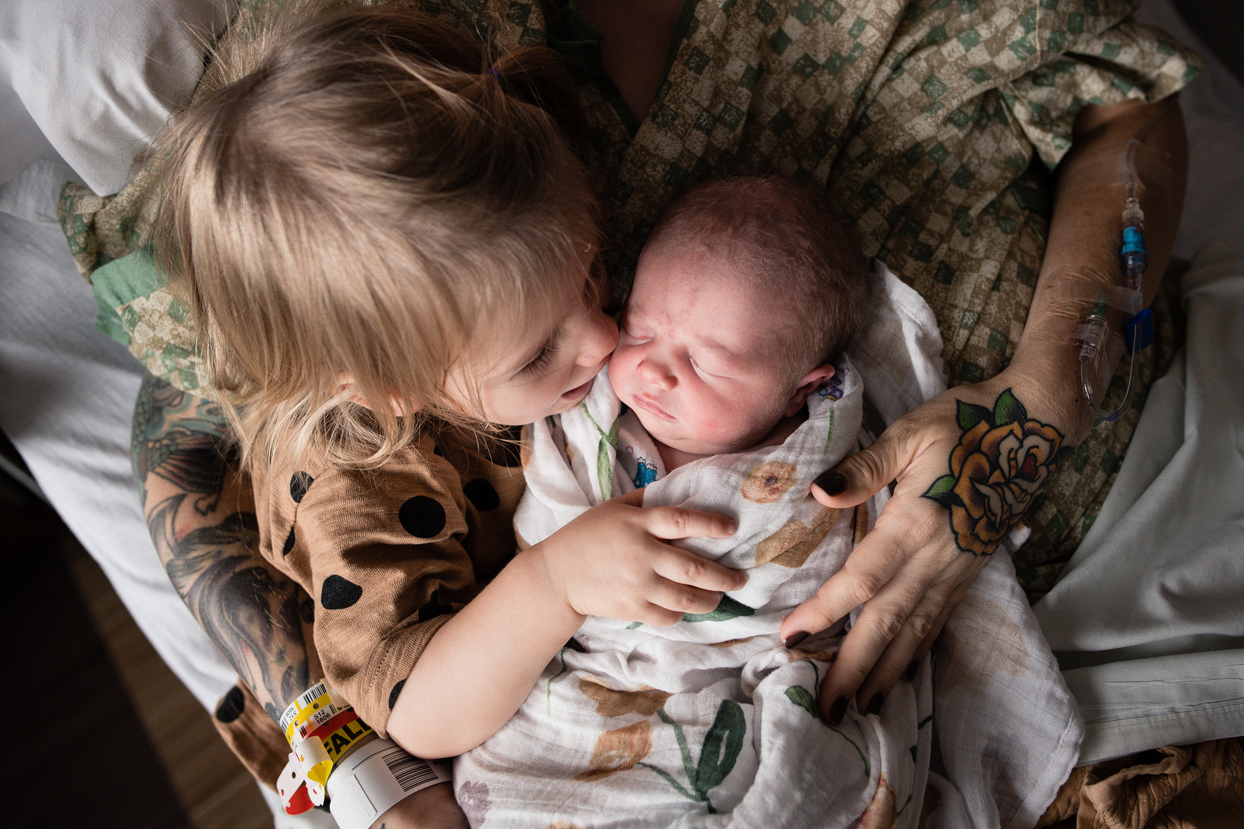 23-big-sister-kisses-newborn-baby-sister-hospital-photography-session.jpg