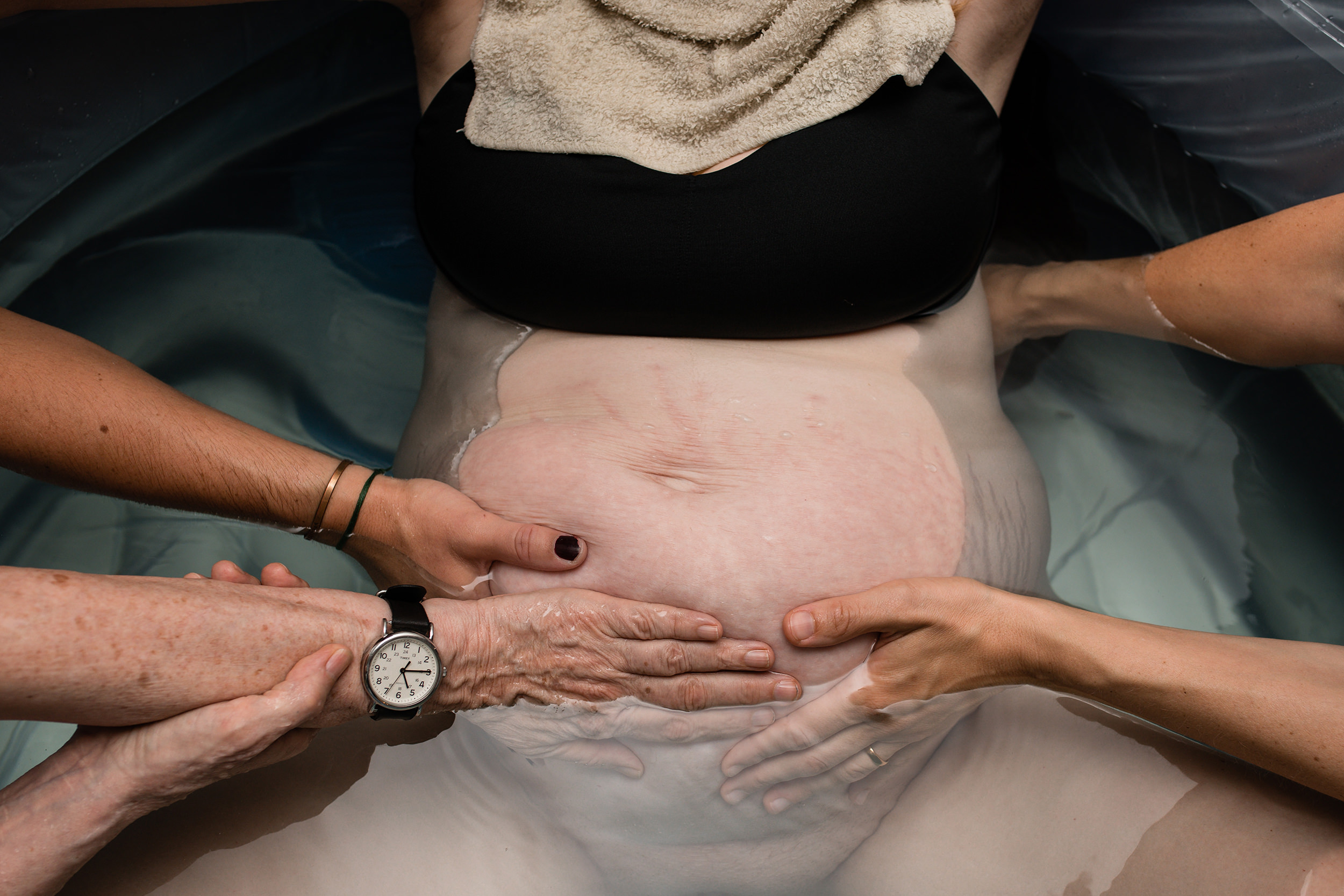 supportive hands on laboring mothers belly during home water birth