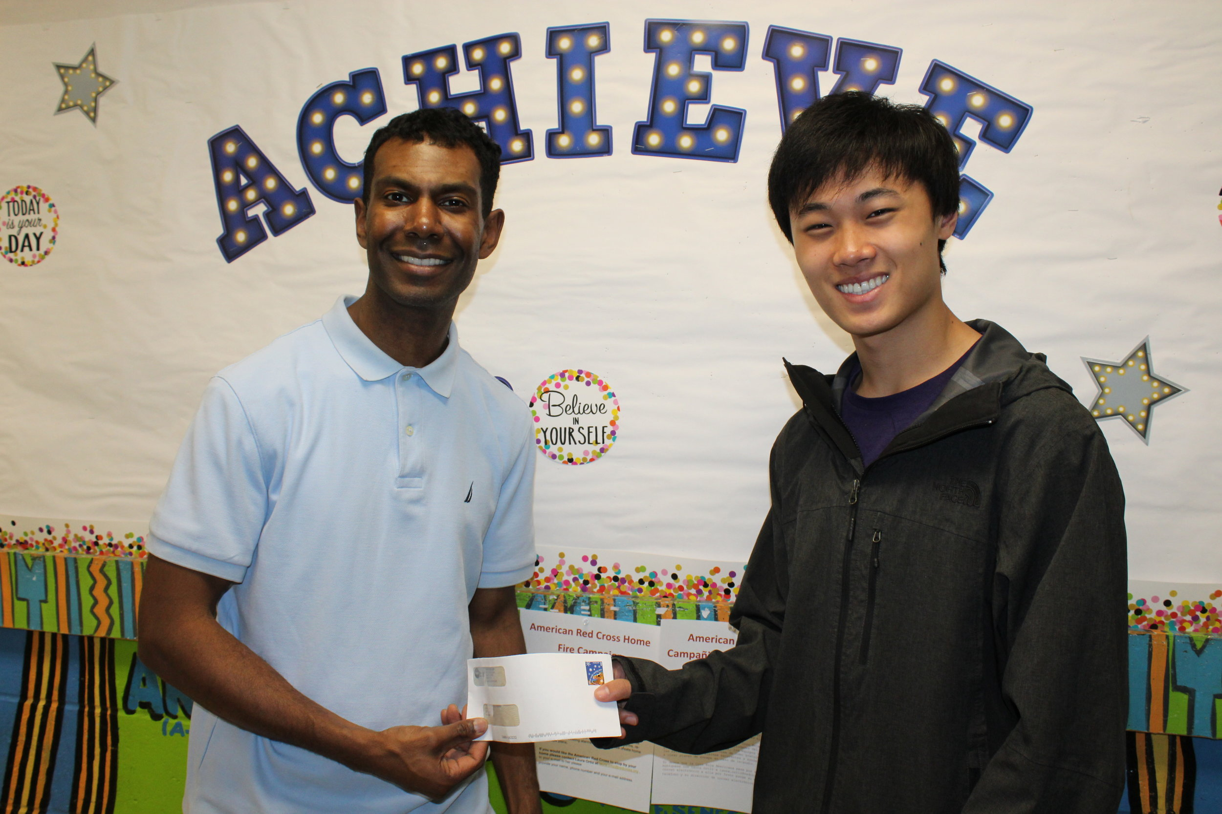 Our (K-5) CASPER Program Manager, Waid Ramsubhag, receives a check from Joshua Zhang
