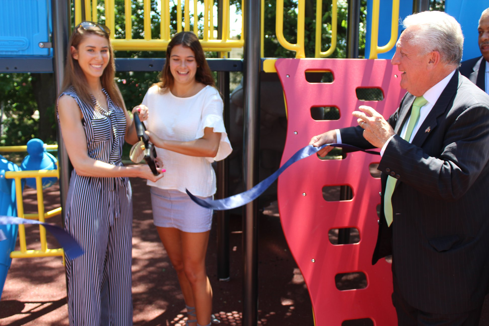 Former New Canaan High School students who helped raise the funds necessary to build the new playground, Becca Walshin now at Penn State and Jackie Newlin, now at the University of San Diego, cut the ribbon with Mayor Harry Rilling assisting.