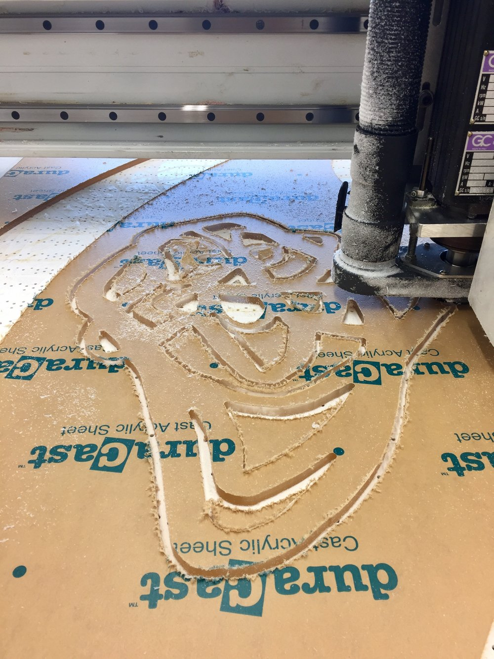 """CNC router cutting drawing into 3/8"""" thick plexiglass."""