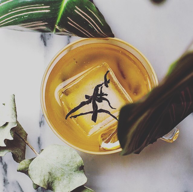 The sunshine and the tropical plant vibe means it's the perfect time for this iced tea riff on an old fashioned. It has also taken me an age to get round to trying this one, but don't get put off by having to infuse the whisky with black tea beforehand - it's super easy even for a lazy sloth like me! • Making tea infused whisky:  Just choose your whisky (ideally something with a bit of punch), pour it into a jar and add loose black tea. A general rule of thumb is about a tablespoon of tea per 200ml of whisky, so make as much or as little as you like. Let it steep for about an hour and then strain (taste it along the way and don't leave it too long, otherwise it will go bitter). • Black Tea Event: 60ml black tea infused whisky 1 tsp honey 2 dashes spiced orange bitters 1 dash aromatic bitters  Stir all the ingredients well and strain into a glass with plenty of ice. Garnish with a few black tea leaves and wheel of lemon if you like. • • • Photo and recipe from the genius that is @todays_tipple #summersips #summertipple #happyhour #imbibe #imbibegram #instadrinks #instadrinkstagram #homebartender #craftcocktails #craftcocktail #riffonaclassic #classiccocktail #classiccocktails #bitters #craftbitters #bitterunion #flatlay #flatlaystyle