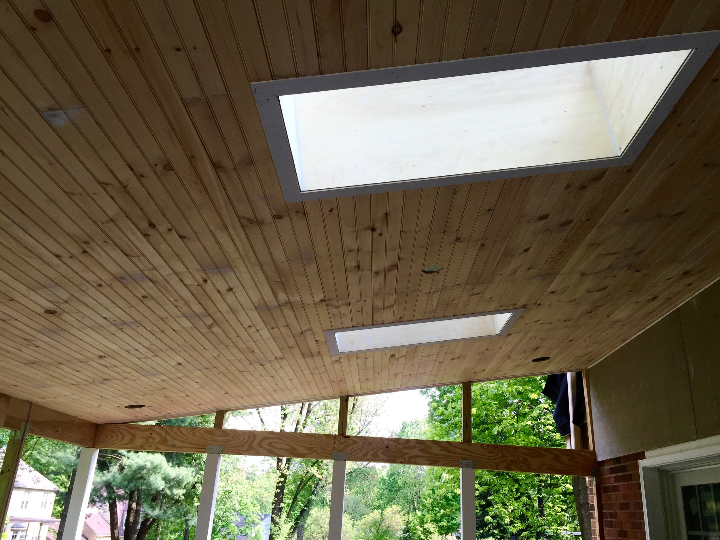 Skylights in beaded board ceiling featured in screened-in porch