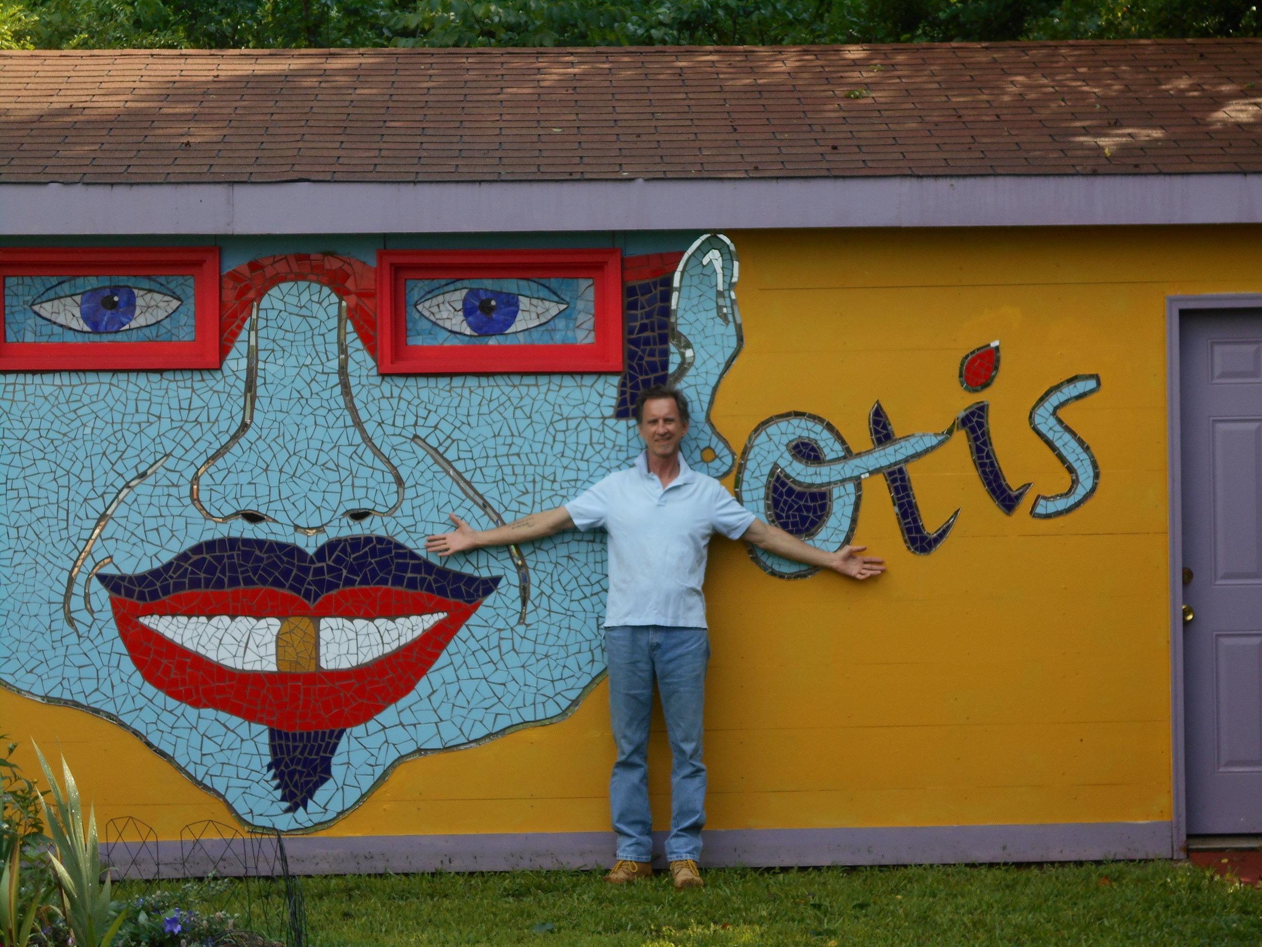 Standing in front of my garage mosaic. Otis is 11 feet from ear to ear and 8 feet from glasses to chin.