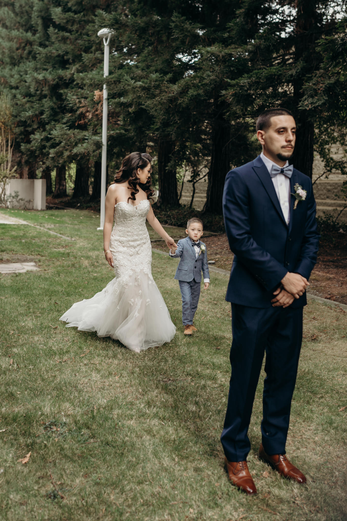 bride and son walking up for first look