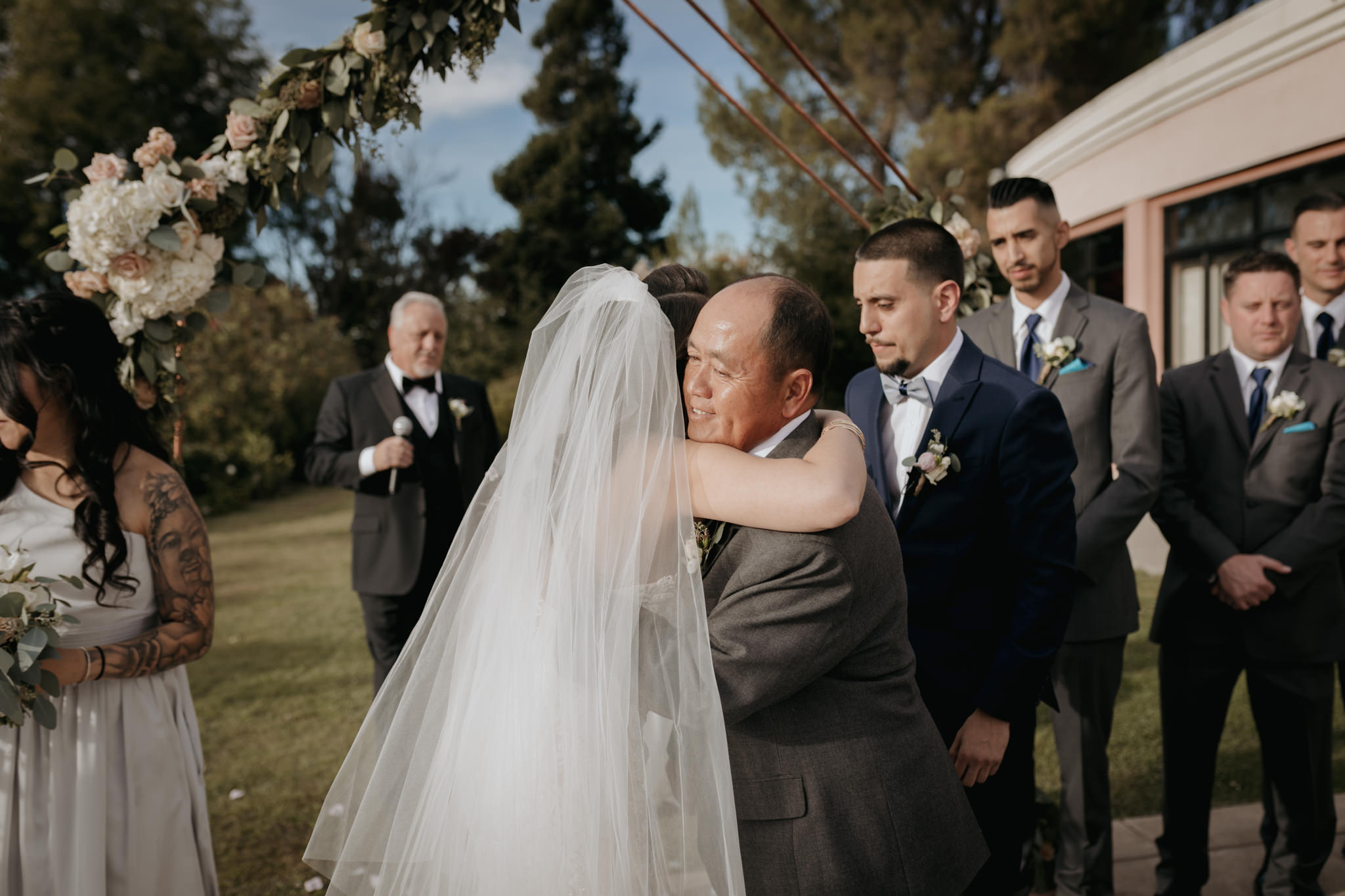 father of bride hugging bride at altar