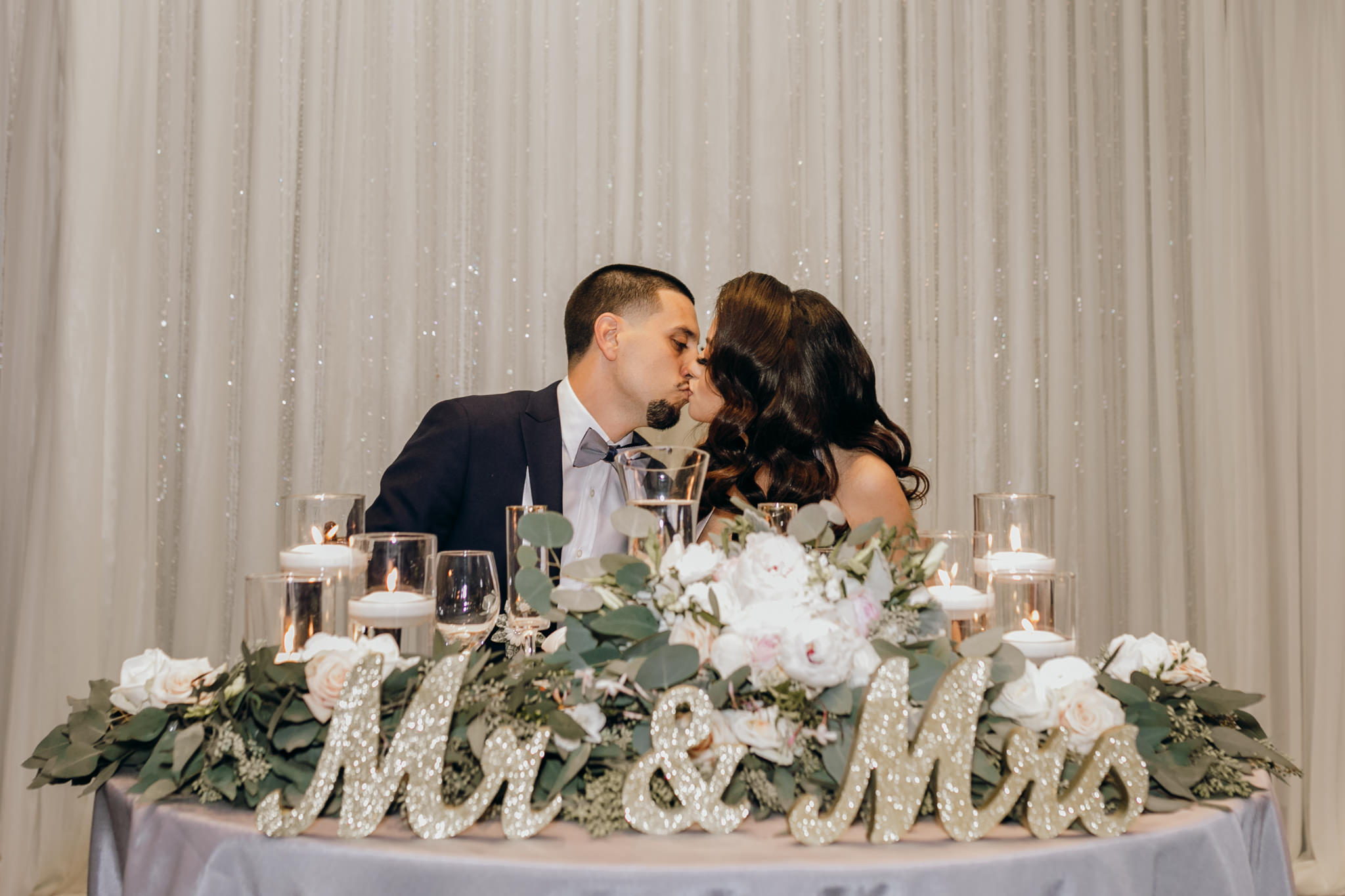 bride and groom kissing at sweetheart table