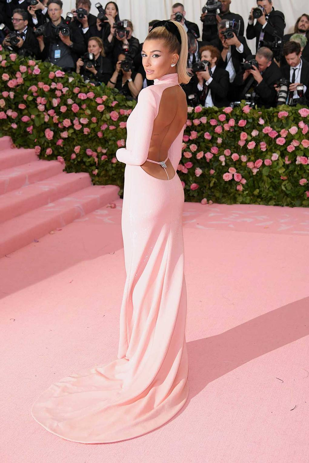 Hailey Bieber wearing Alexander Wang - Wang does no wrong! I love this cute gown which highlights Hailey's cheeky side. Who know a G-sting backless dress could be so cute?! This high neck pastel pink sequin design screams millennial camp, finished off with Bvlgari diamond earrings and a classic black bow with perfect pony tail.