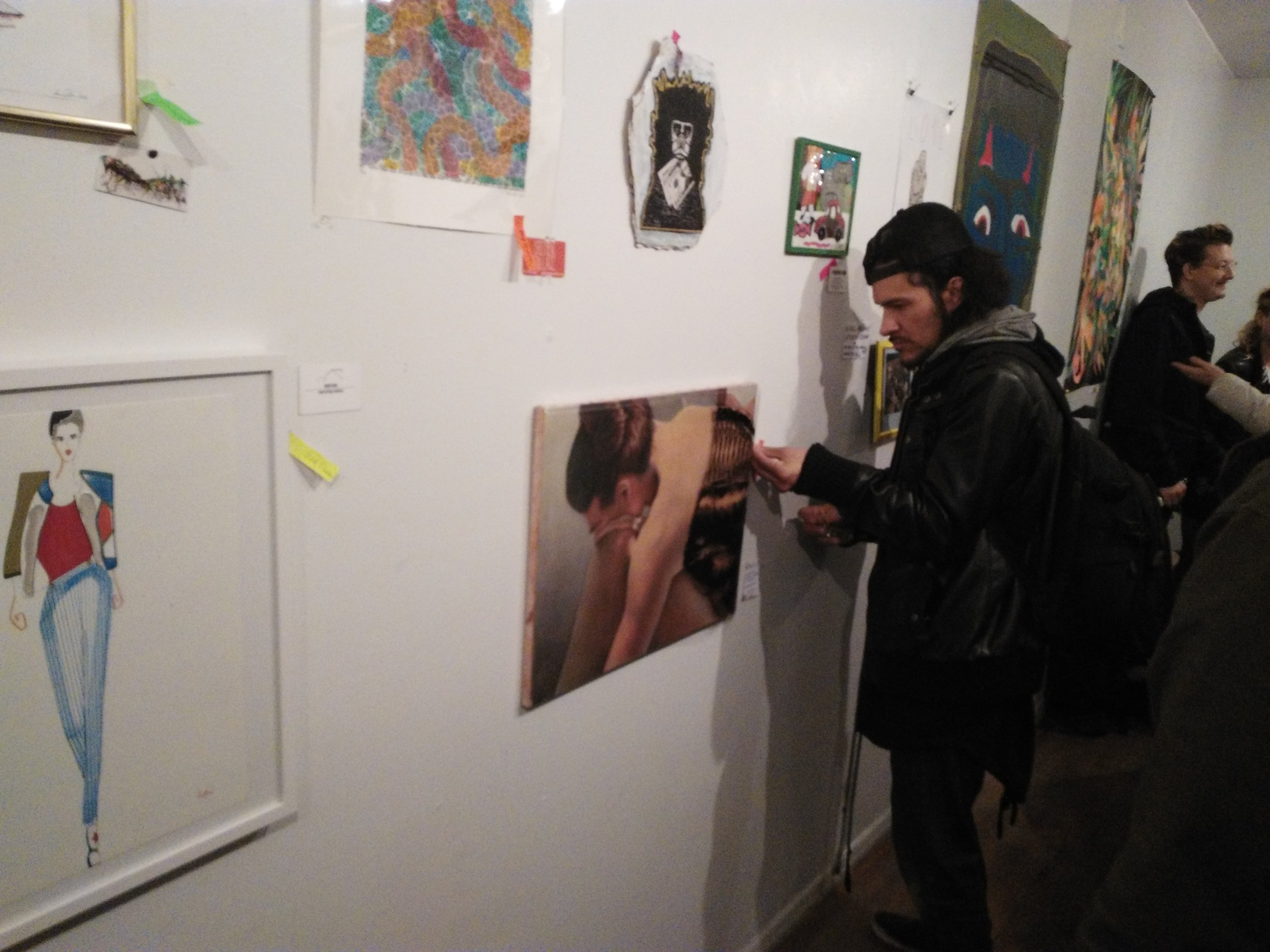 A man places a signed Post-it next to a piece of art to claim it. Just a few minutes into the event, all of the artwork had already been claimed.
