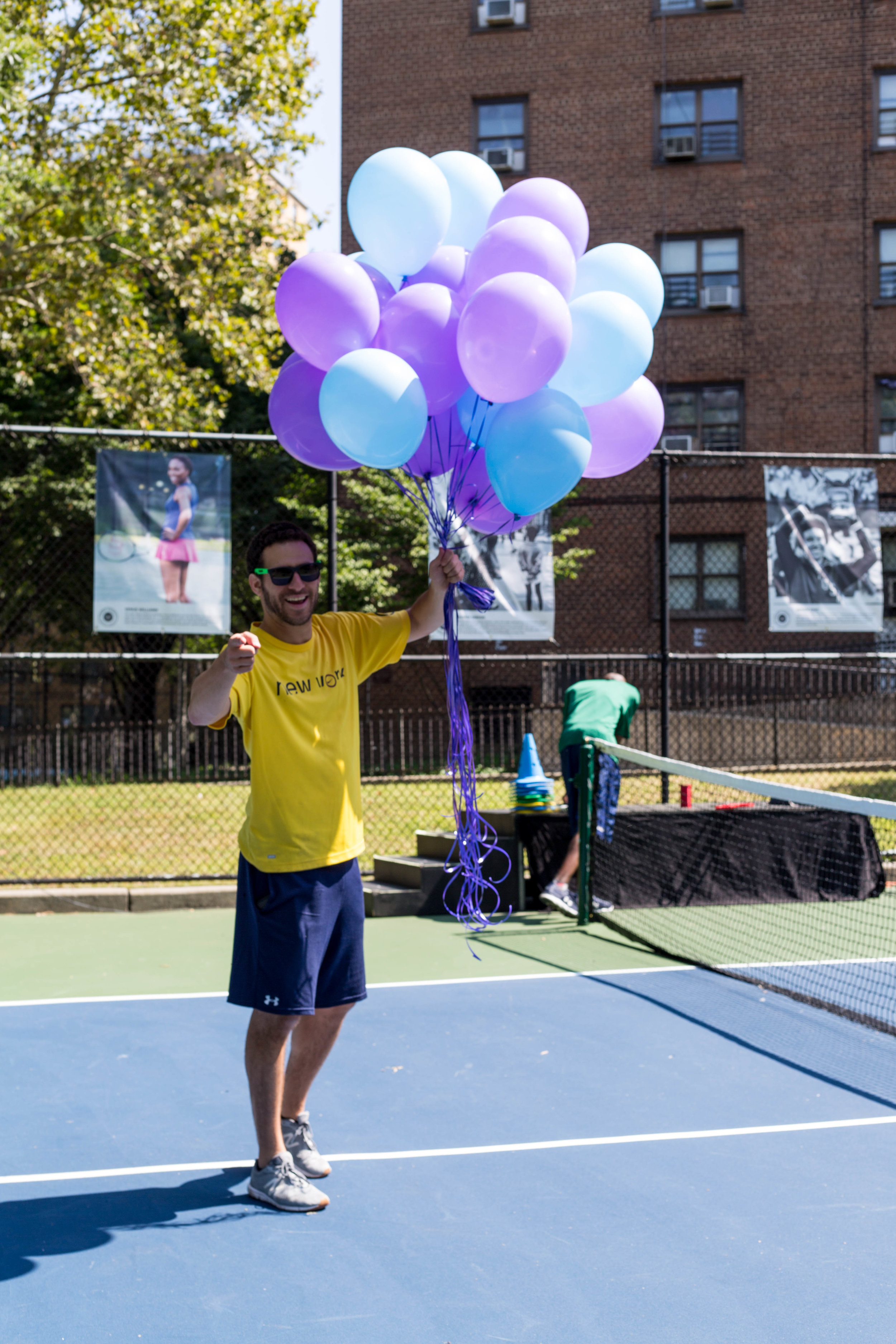 Volunteer Chase Atneu sets up for the community ribbon cutting at the Sumner Housing Project Tennis Court.