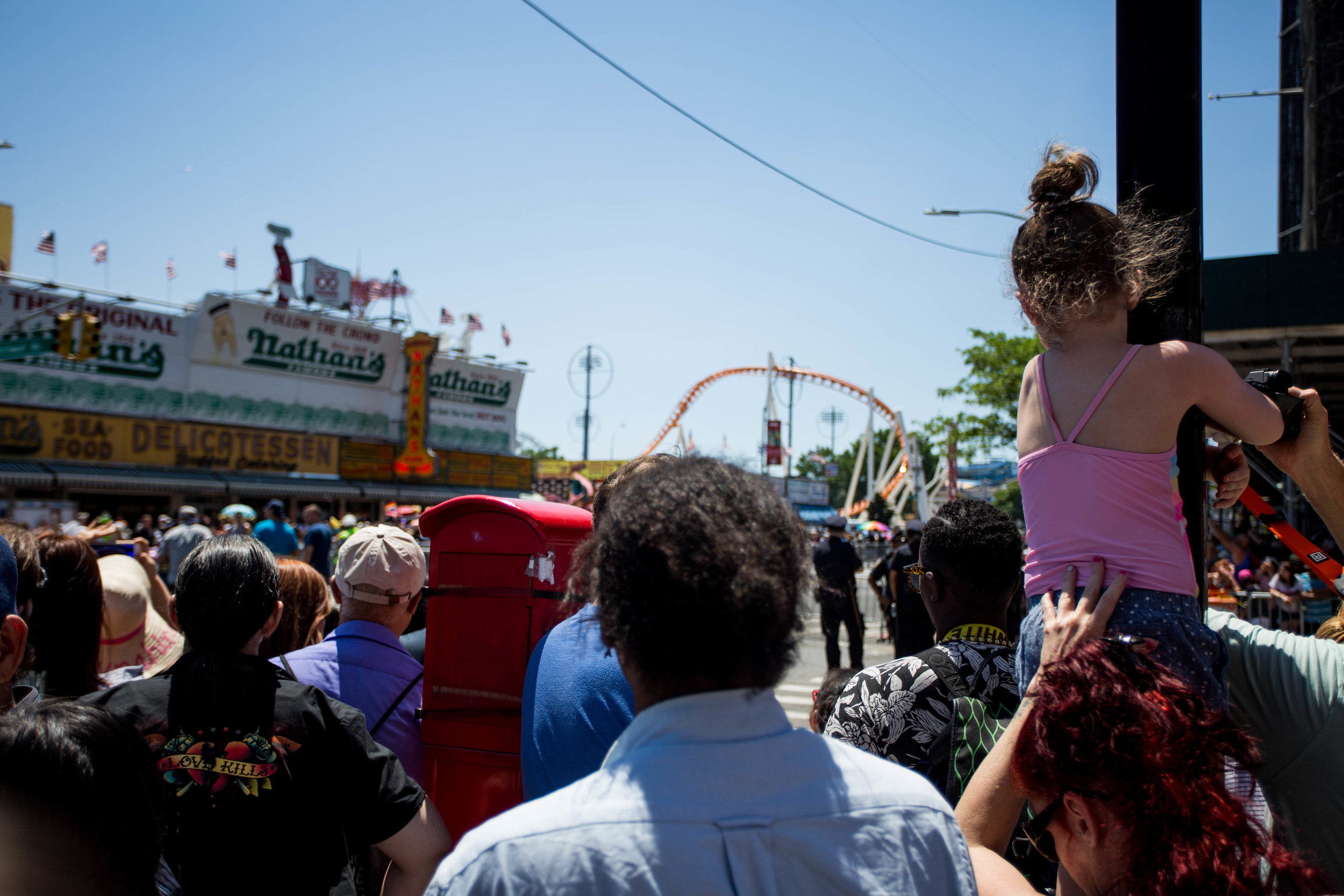 A mother holds her child up in odrder to get a better view over the crowd at Coney Island's 36th anual Mermaid Day Parade, on Saturday June 16, in New York. Photo: Wes Parnell