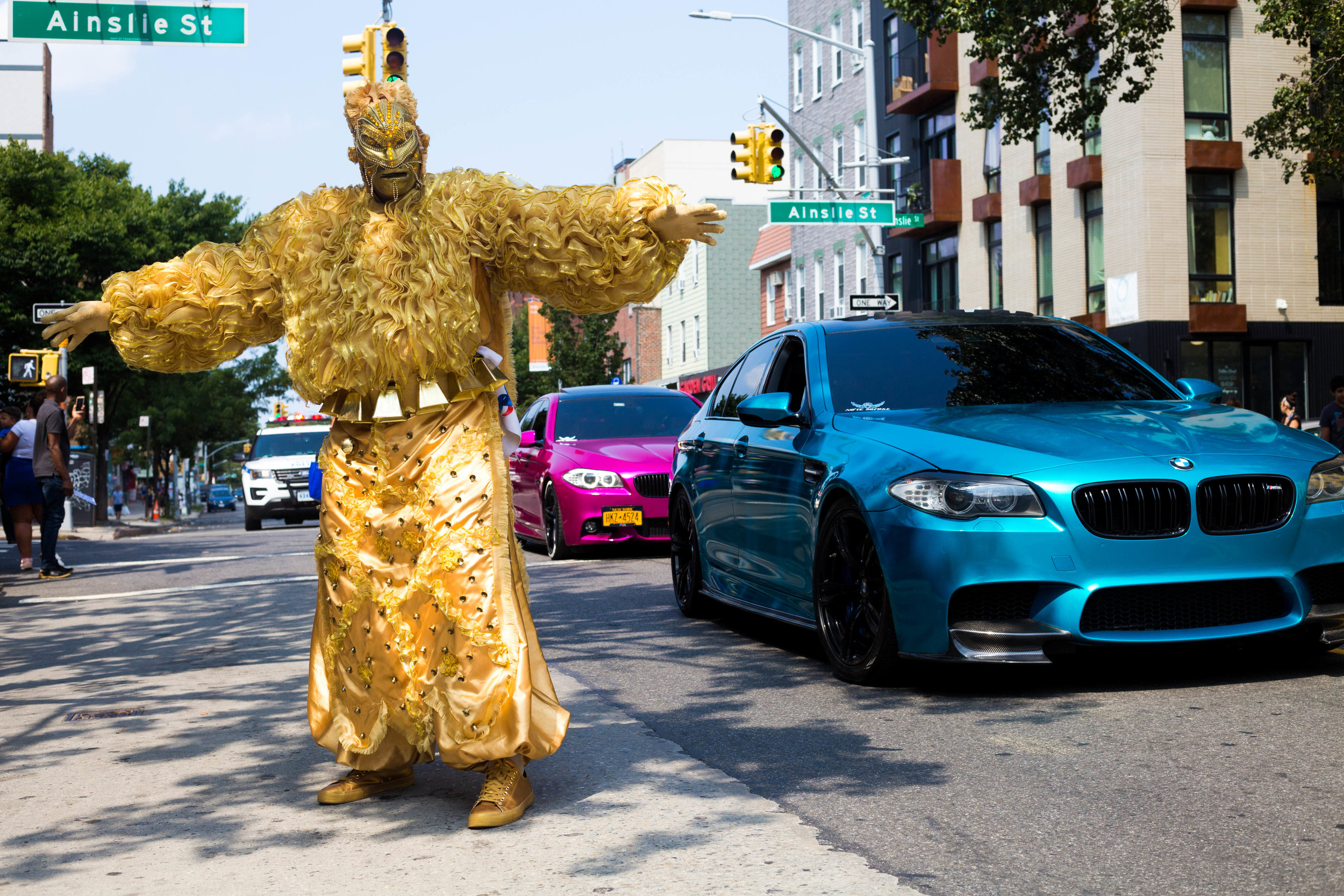 A man in a carnival costume poses for a photo next a pimped out BMW at the 18th annual Williamsburg Dominican Parade, on Sunday, Aug 26, in New York. Photo: Wes Parnell
