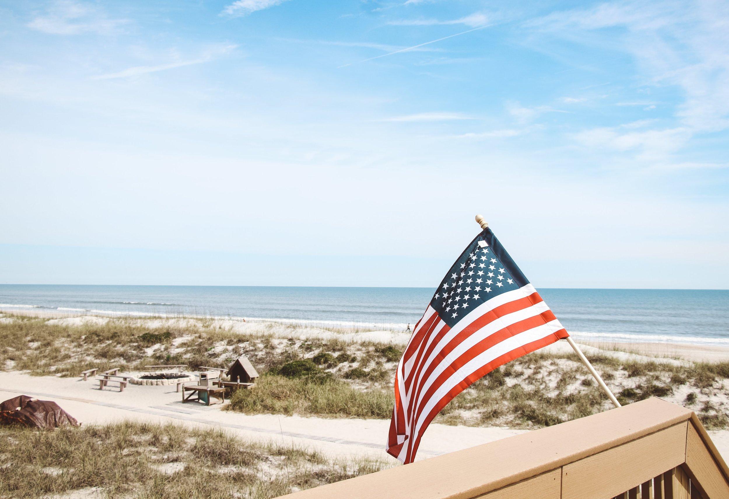 American flag waves over the Atlantic coast in Jacksonville, Florida    Photo by  David Masemore  on  Unsplash .