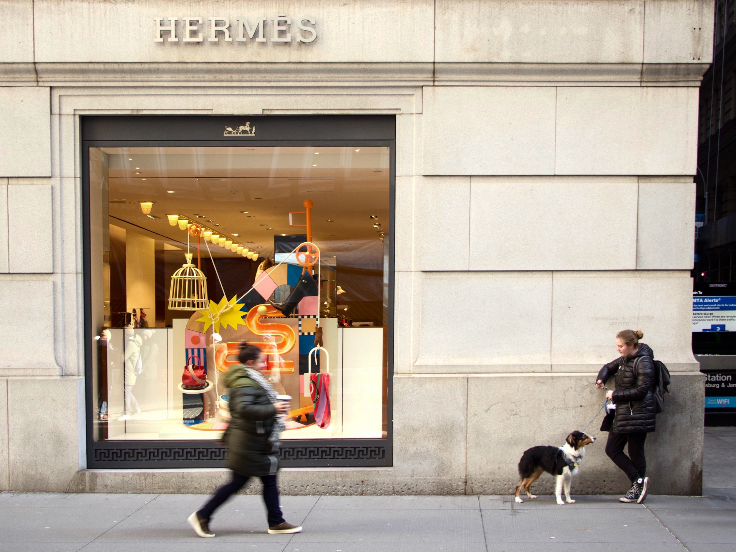Woman with dog stands outside luxury store, Hermes, on the corner of Exchange Place and Broad Street in the Financial District, NYC. || Photo credit to Gabriela Kressley.