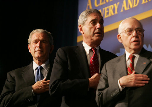 President George W. Bush joins FBI Director Robert Mueller and U.S. Attorney General Michael Mukasey during the playing of the national anthem Thursday, Oct. 30, 2008, at the graduation ceremony for FBI special agents in Quantico, Va. || White House photo by Joyce N. Boghosian