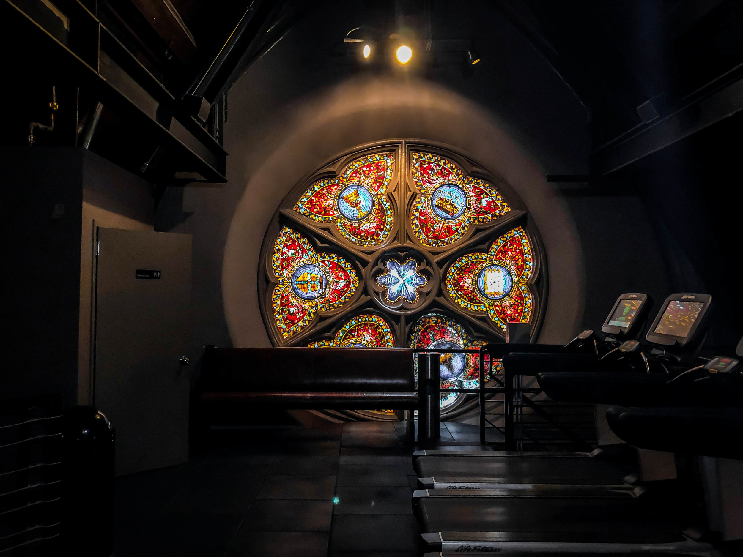 The treadmills are illuminated by the stained glass window left by the former Episcopal church in Chelsea, Manhattan on Feb. 10, 2019. || Photo by Bernadette Berdychowski.