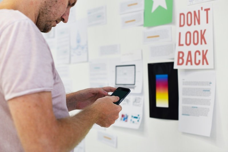 man looking at phone in front of bulletin board