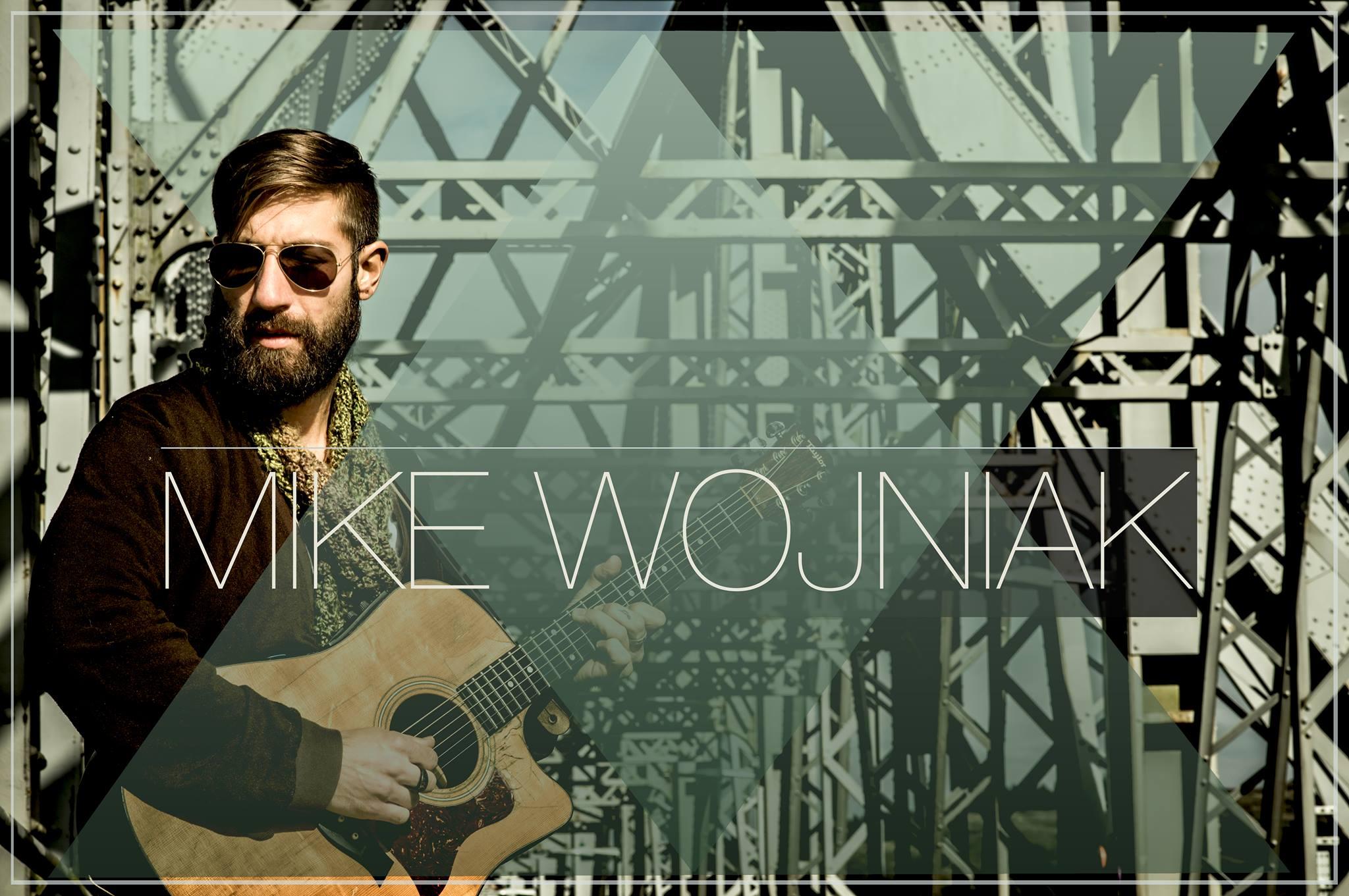 Mike Wojniak with his guitar on a bridge.