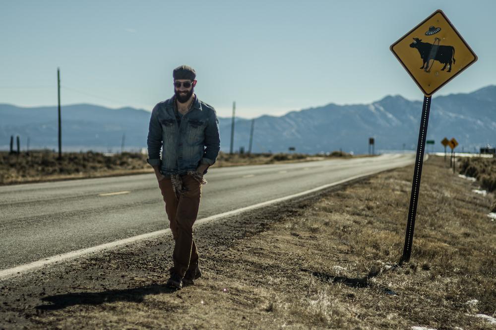 Mike Wojniak walking down a Colorado roadside.