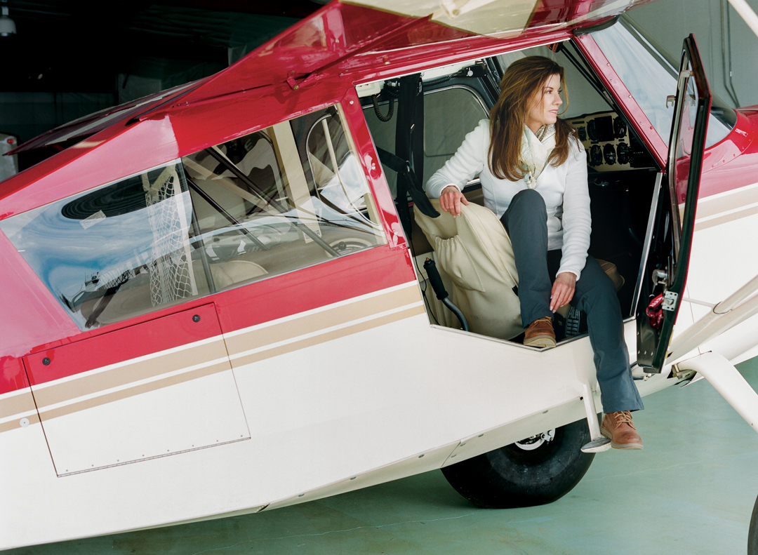 lori_olson_women_in_wyoming_chapter_2_filling_the_void_backcountry_pilot_with_papa_charlie_her_plane_in_pilots_seat.jpg