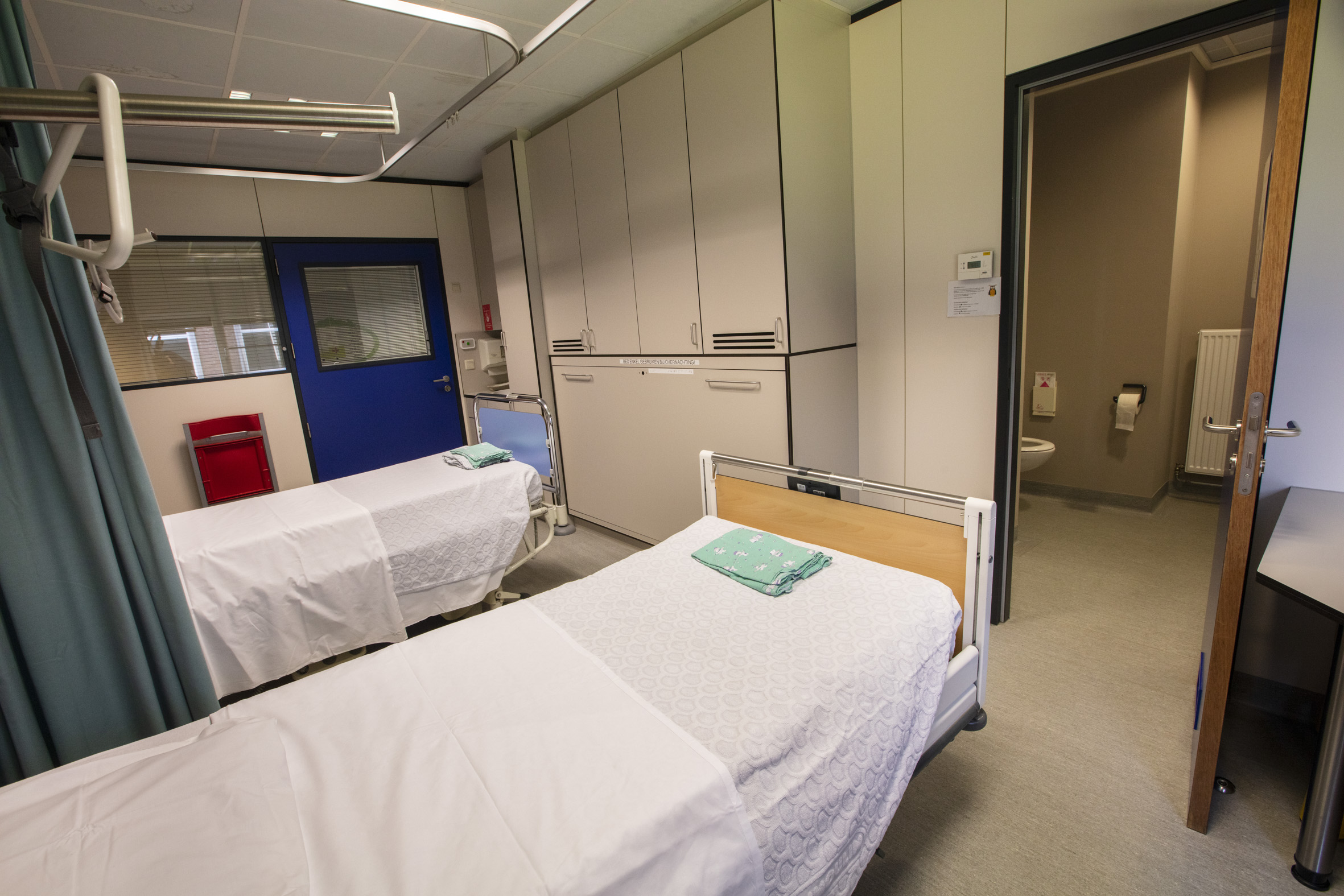 Een tweepersoonskamer met ziekenhuisbedden