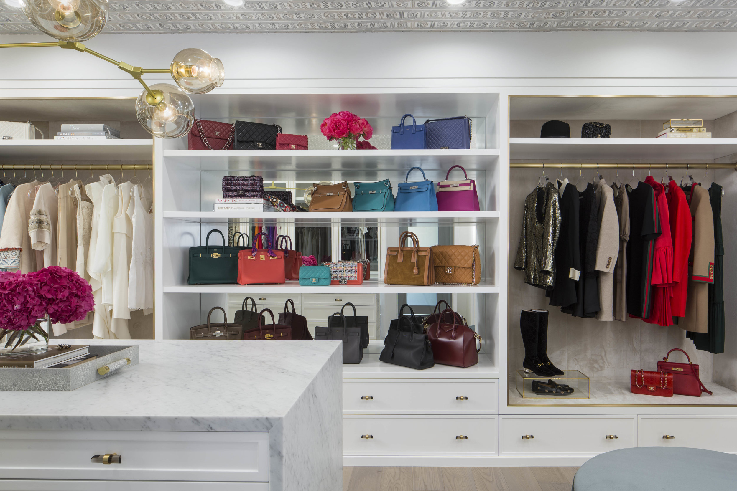A MIRRORED HANDBAG DISPLAY IS THE CENTERPIECE FOR THE ROOM, FLANKED BY SUEDE-LINED STAGING AREAS WHERE THE CLIENT CAN ASSEMBLE LOOKS AND DISPLAY HER FAVORITE NEW PIECES!