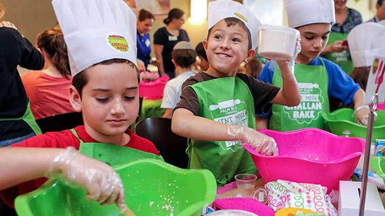 Landon McCoy (center), 8, lifts a cup of ingredients while making challah, Sunday, February 21, 2016 at Palm Beach Synagogue, along with Elad Friedman (left), 8, and Michael Liberty (right), 8. The event was billed as the First Ever Palm Beach Community Mini Mega Challah Bake, and organizers estimated that around 100 young people came out to participate. Damon Higgins / Daily News
