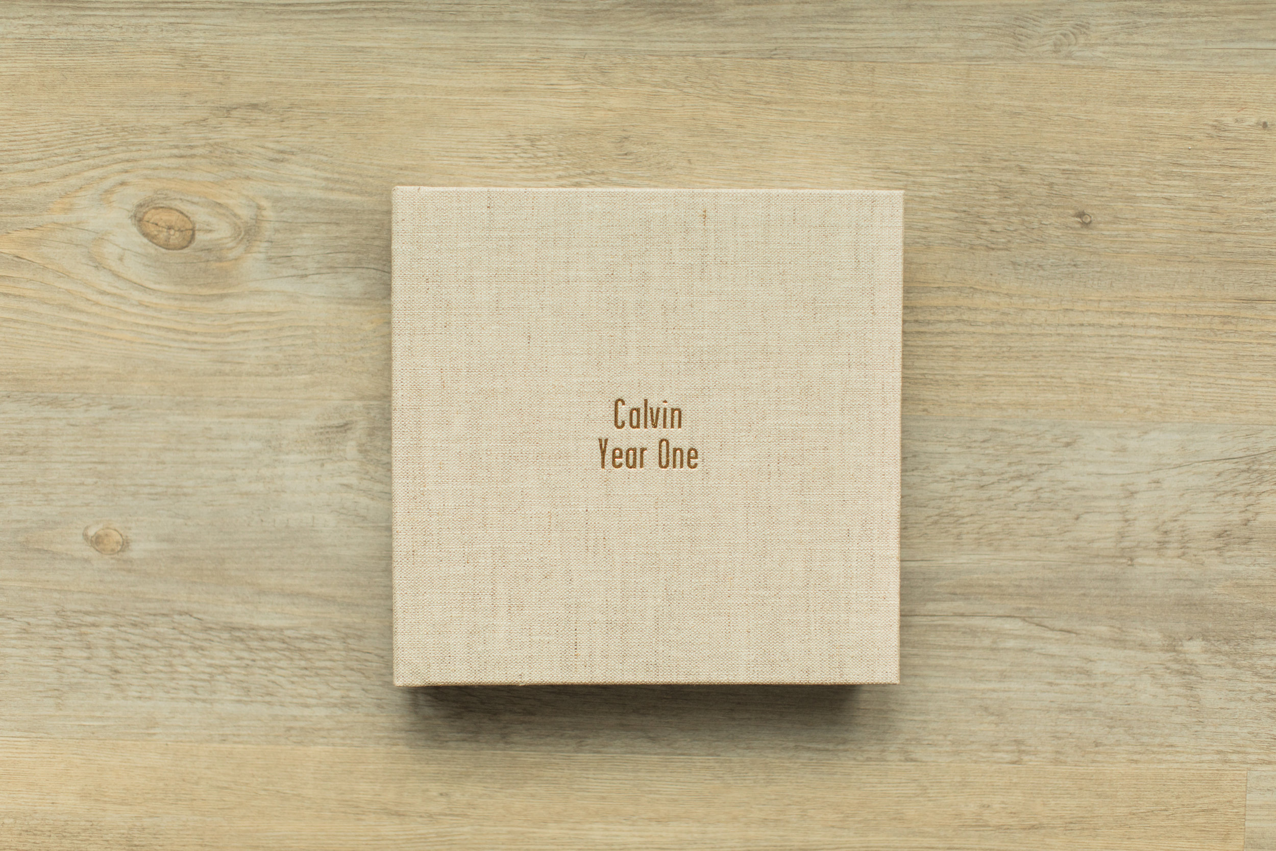 A baby photo album sits on a wooden table.
