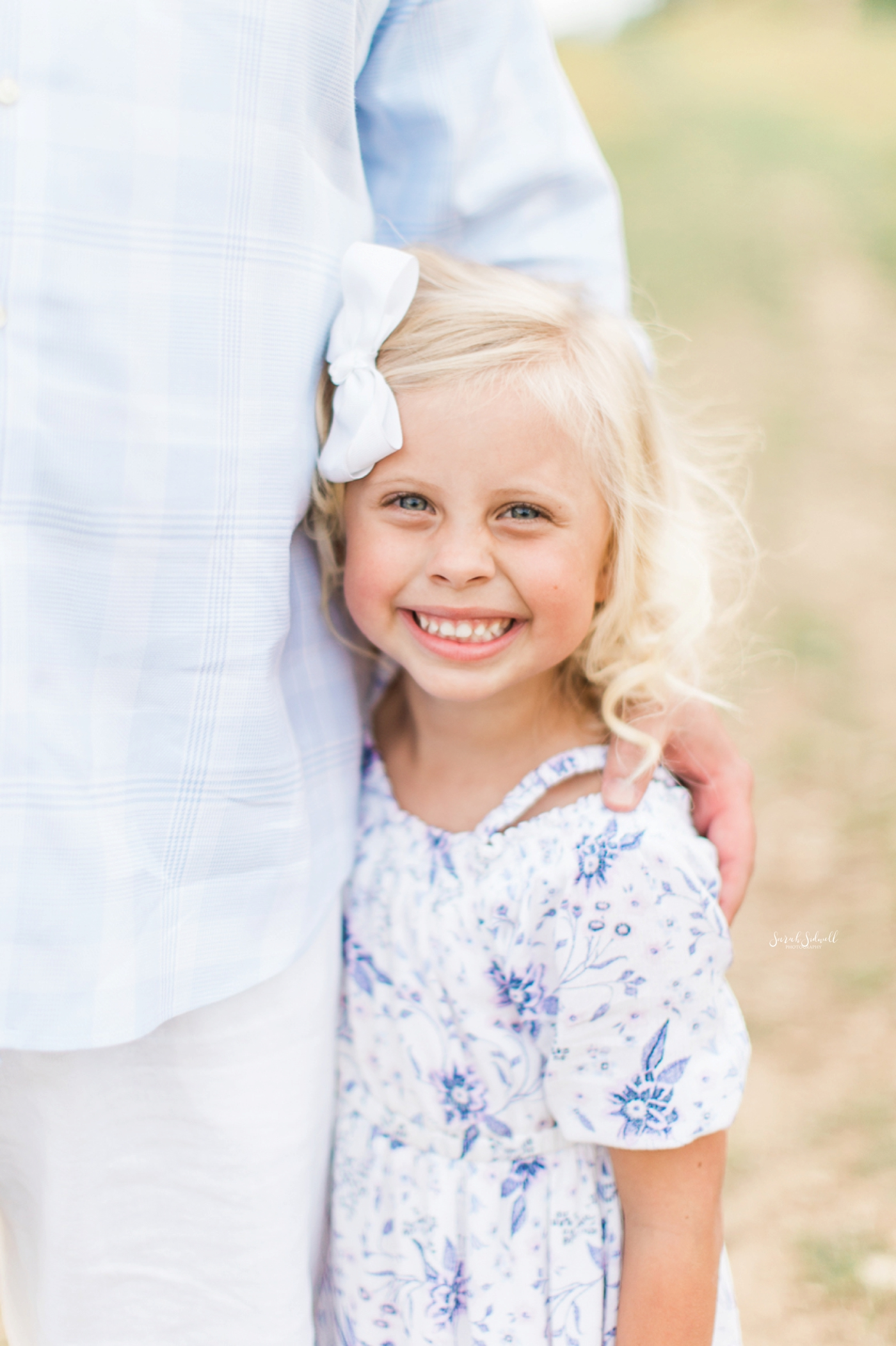 A girl hugs her dad during some family photography photos.