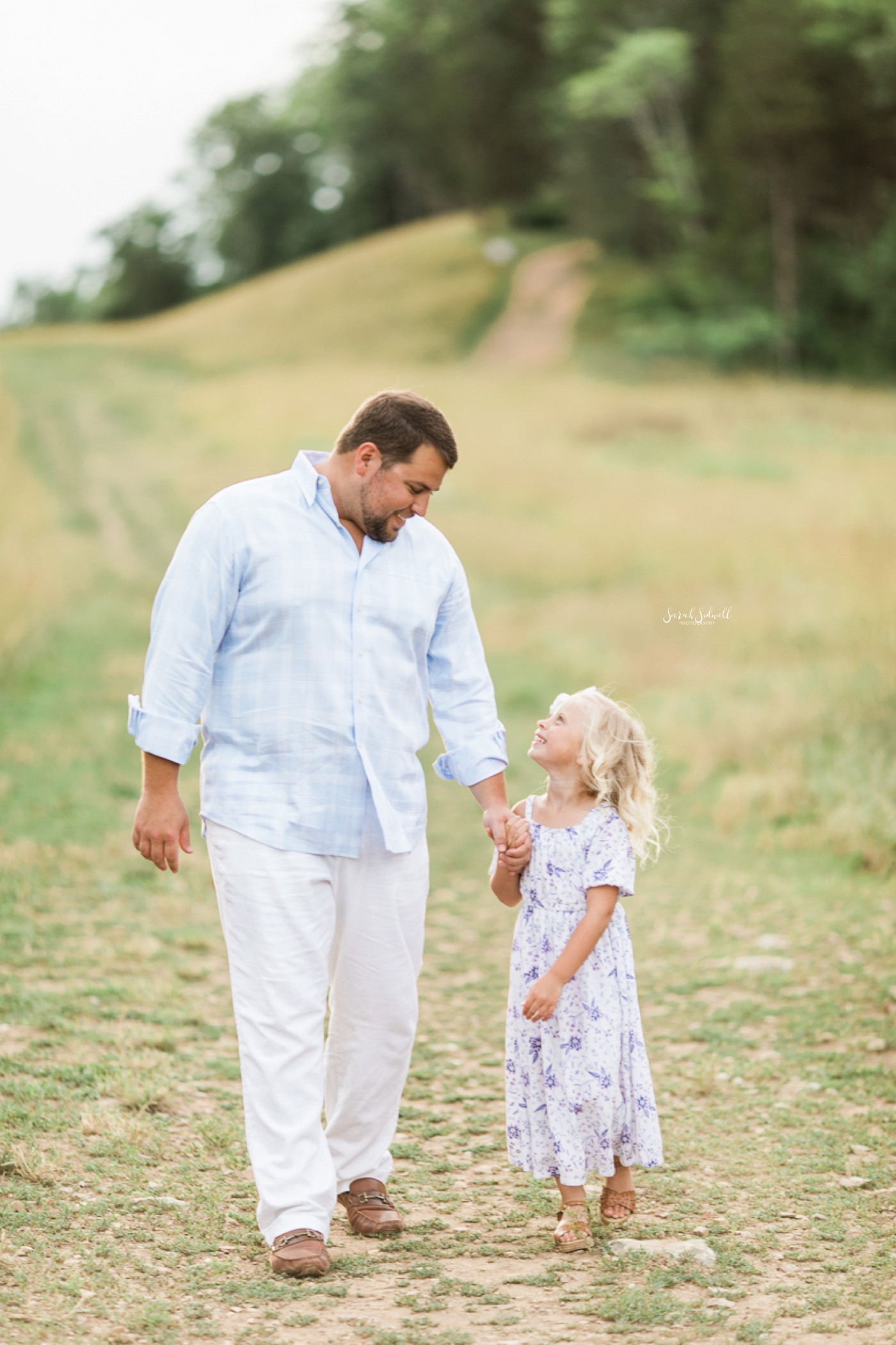 A dad walks with his young daughter.