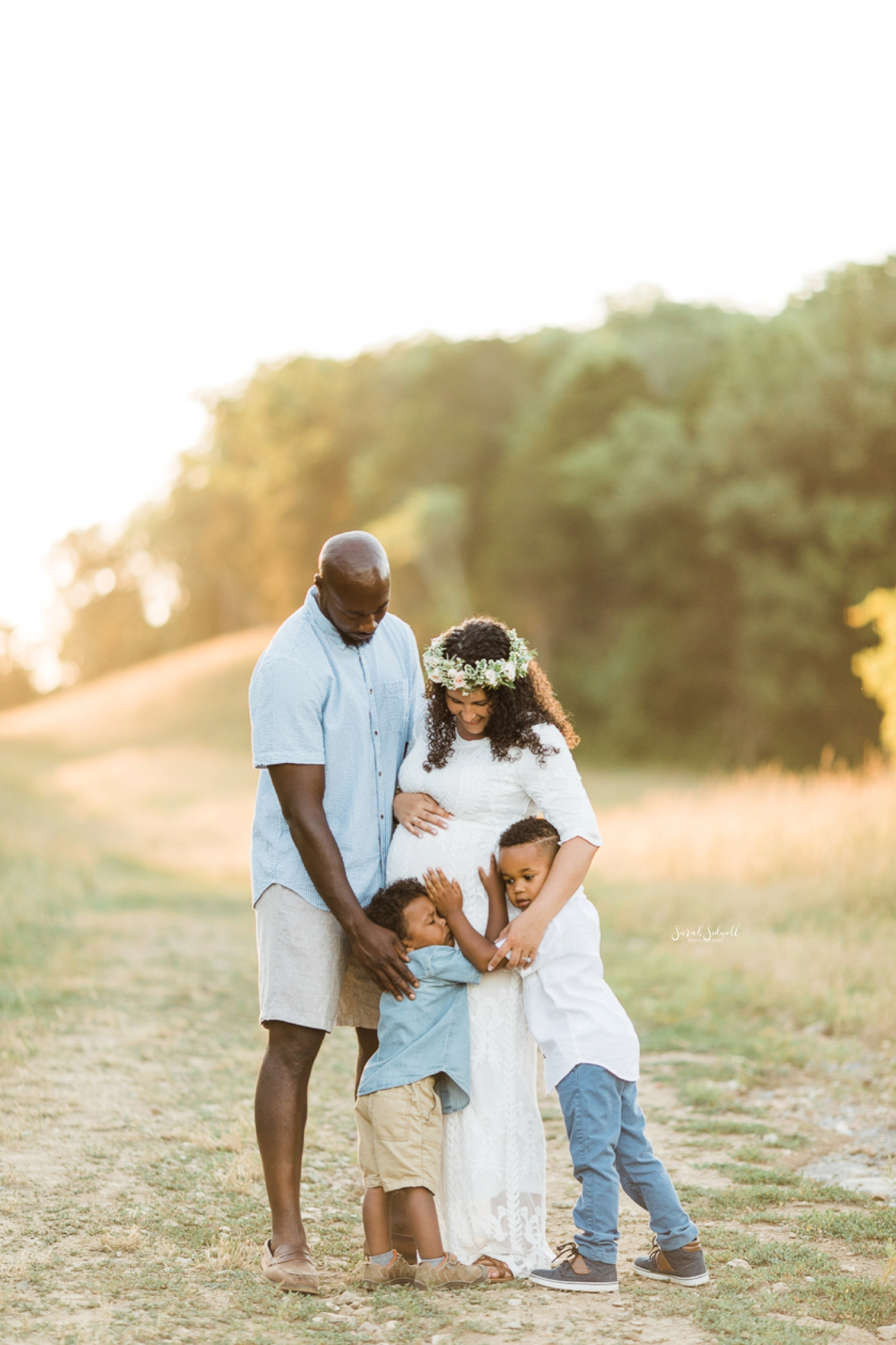 Two parents hug their sons during a family maternity session.