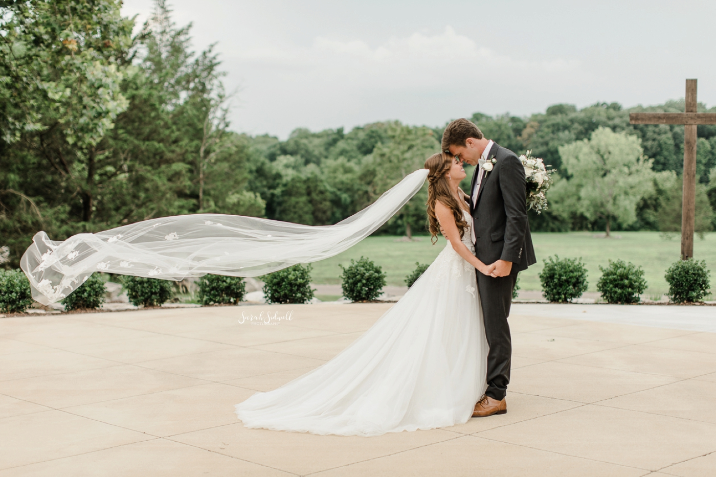 A bride's veil blows in the wind as she kisses her groom.