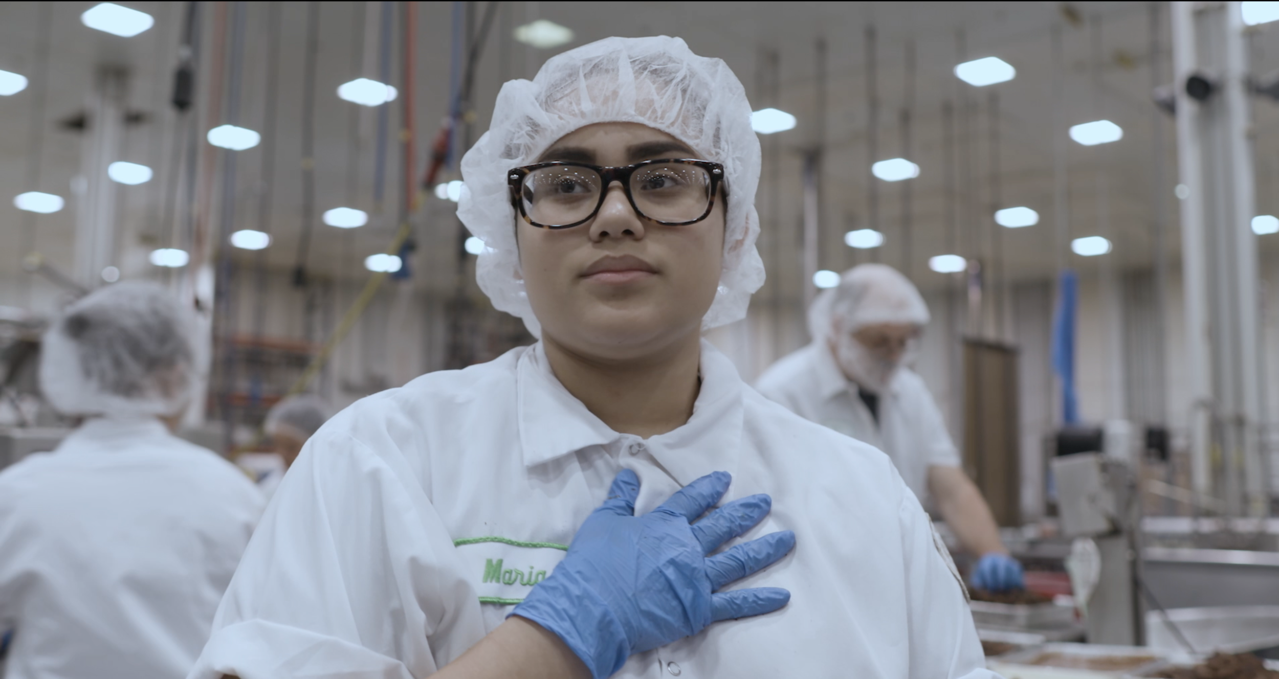 "Maria works the line in the Sweet Street desert factory in Reading, PA. Still from the film ""Behind Closed Doors."" Credit: Axel Baumann."
