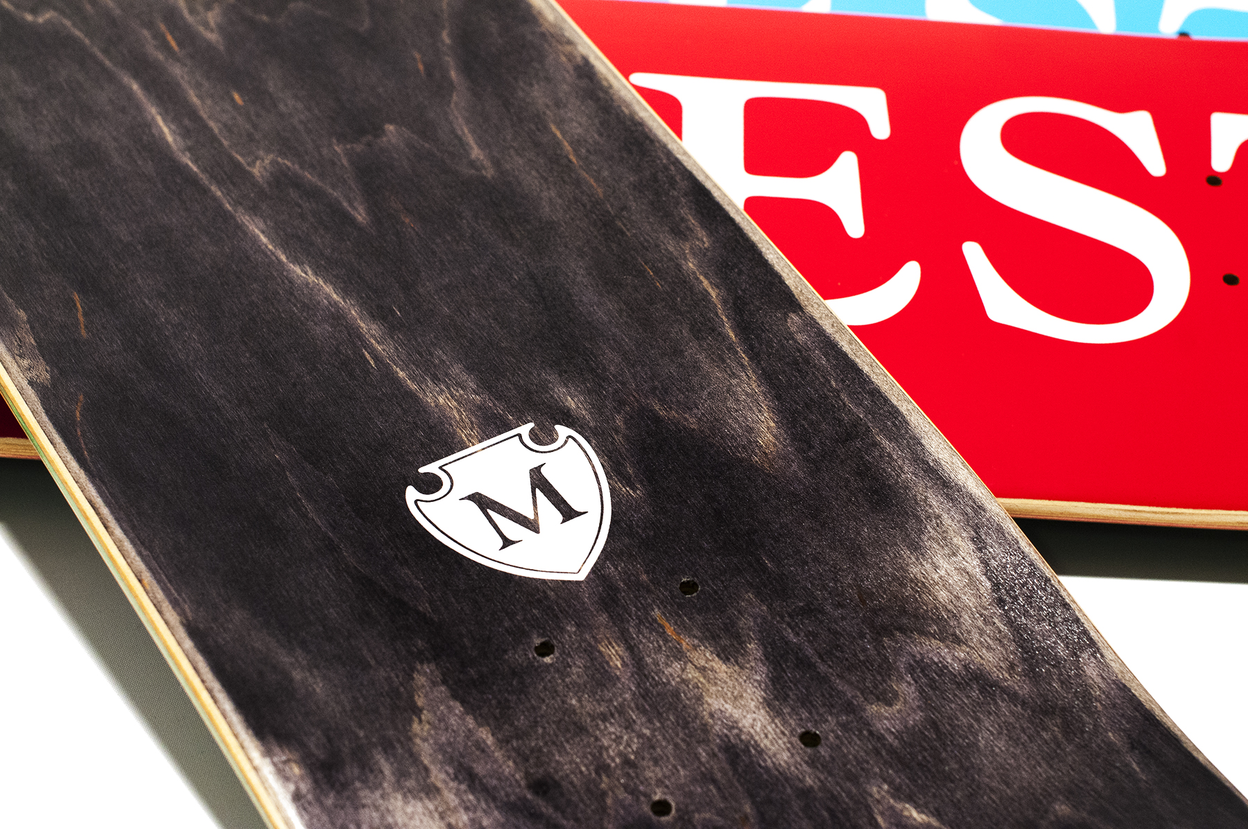 Modest Logo Skateboard Deck: Shield icon top graphic.