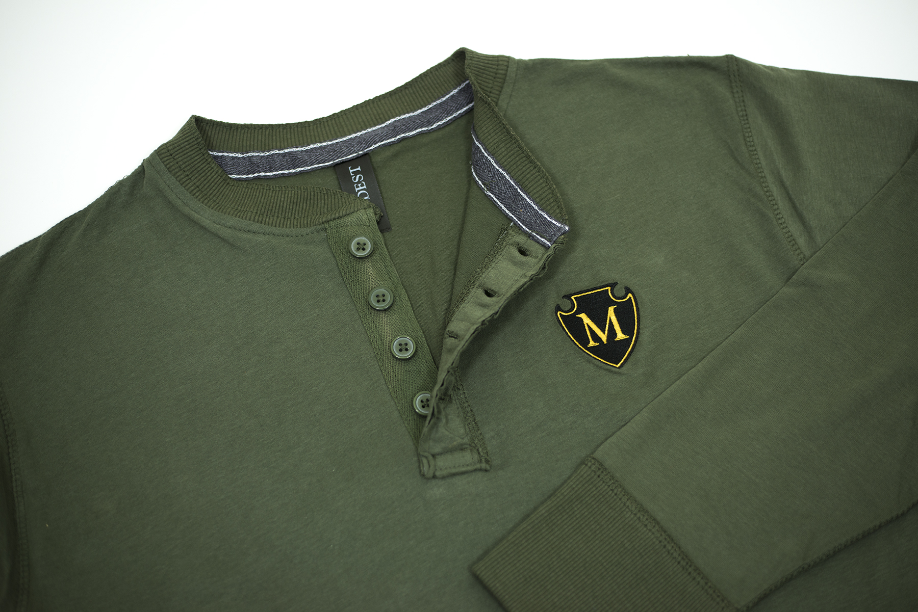 2 Color Emboidered Shield: Placed on long sleeve henley's, with custom inside hang tags.
