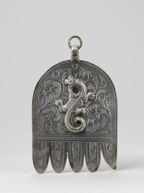 Pendant. Maghreb, Morocco, Casablanca, early 20th CE. Made by Jewish artisans. Outfit of both Jewish and Muslim women. Talisman against the evil eye. The salamander is a positive symbol in Jewish tradition. Silver, engraved and chiseled, 12,2 x 8,2 x 1,2 cm, 79 g. Inv. 74.1965.2.2. Photo: Michel Urtado / Thierry Ollivier.    Location:   Musee du Quai Branly, Paris, France    Photo Credit:   © musée du quai Branly - Jacques Chirac, Dist. RMN-Grand Palais / Art Resource, NY    Image Reference:   ART522175