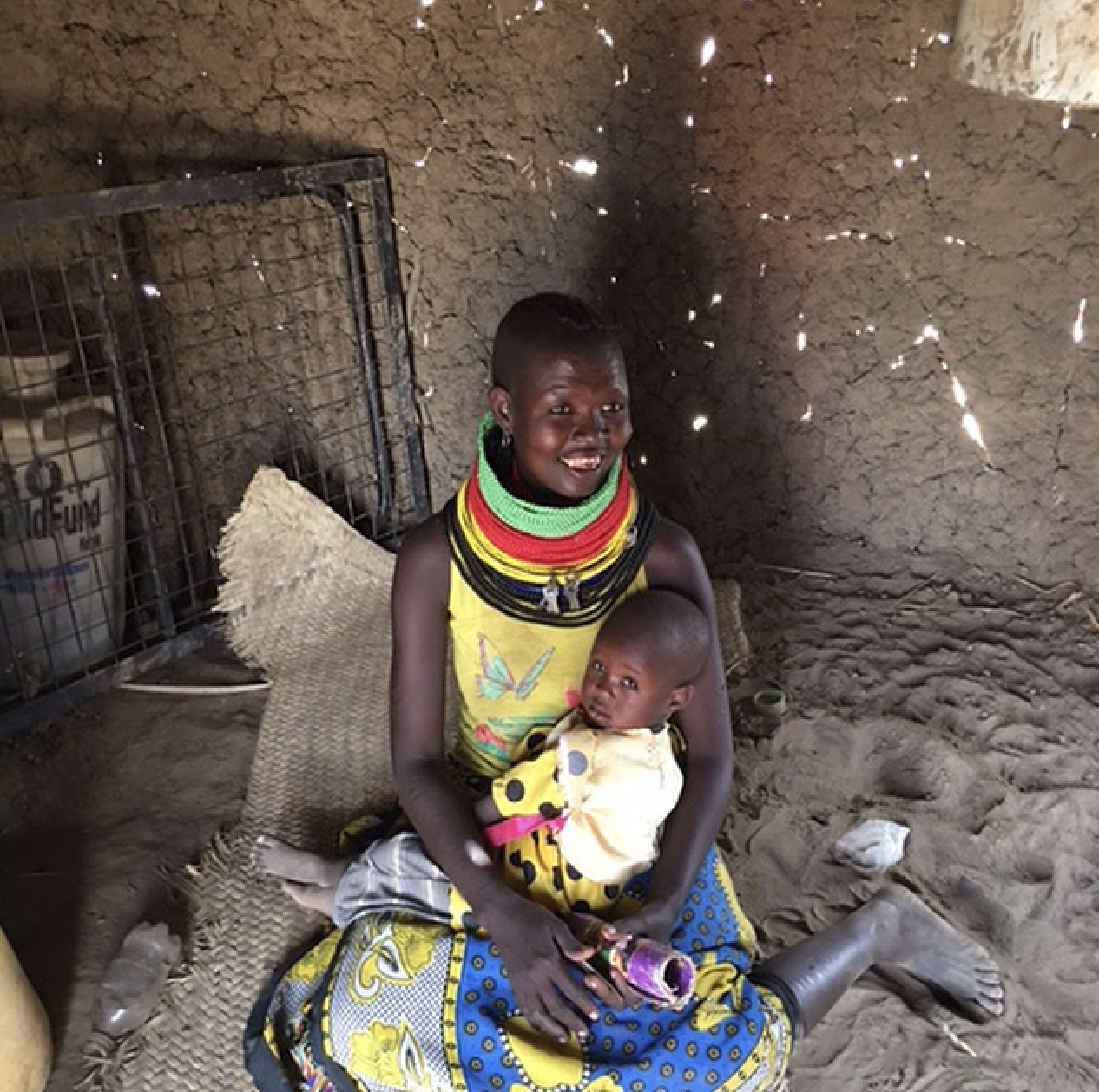Mom, Lowoto, with her 2-year-old son. Her family has lost all of its livestock.
