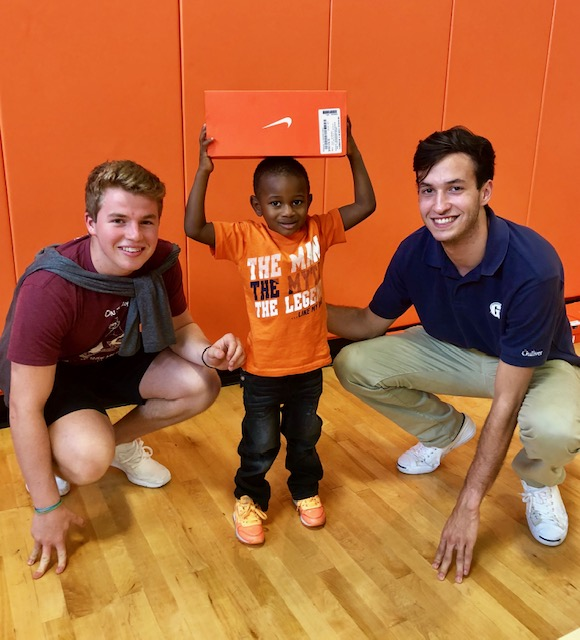 Kicks for Kids Gibson founders Nikolas Aixala and Connor Sazant with a young recipient.