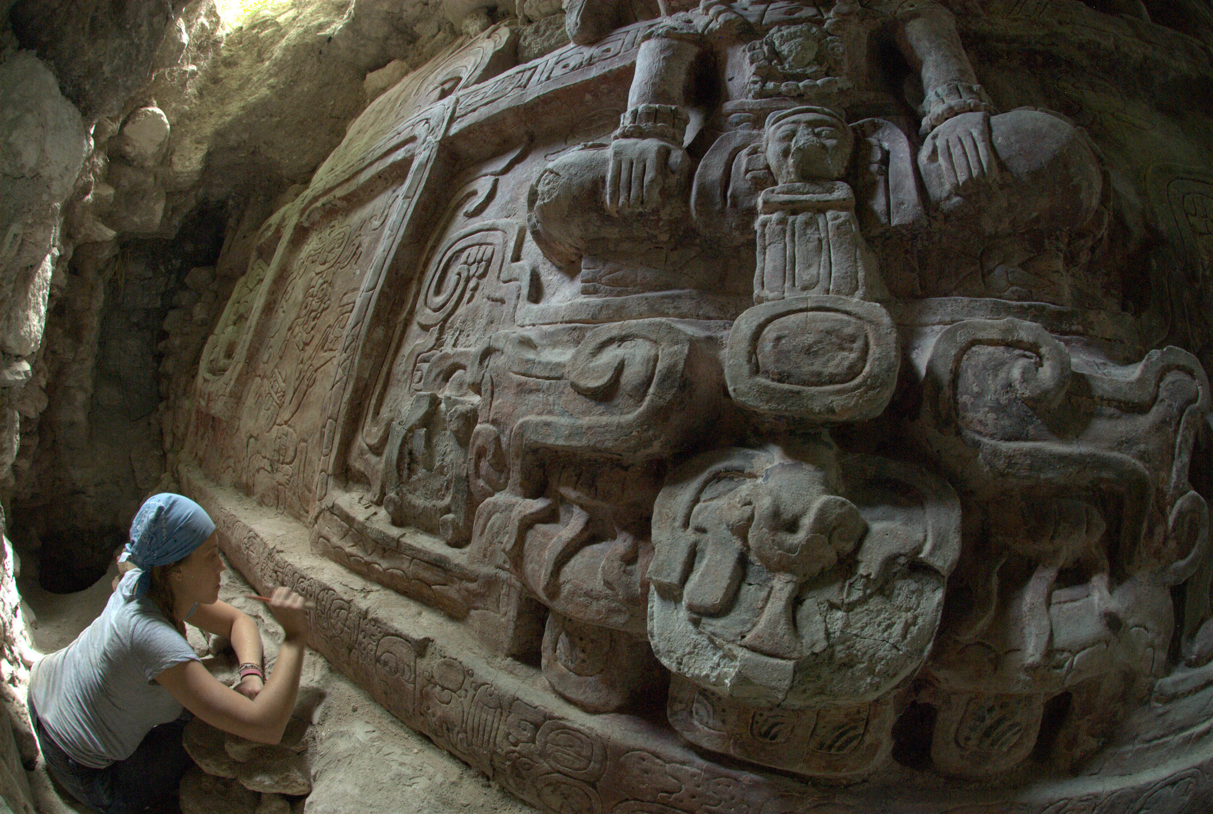 Archaeologist Anya Shetler cleans an inscription below an ancient stucco frieze recently unearthed in the buried Maya city of Holmul in the Peten region of Guatemala. (Photo: cbsnews.com)